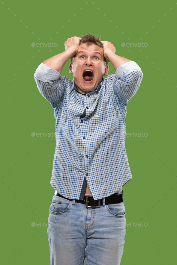 Portrait of the scared man on green - Stock Photo - Images