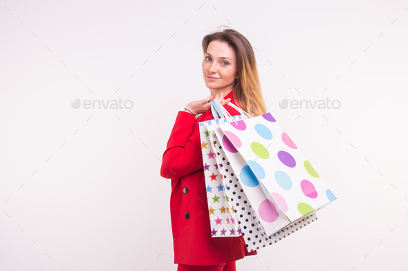 Portrait of beautiful woman in red jacket with shopping bags on her back with copy space. - Stock Photo - Images