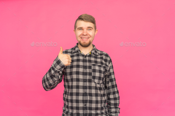 Happy caucasian bearded man with thumb up in pink studio - Stock Photo - Images
