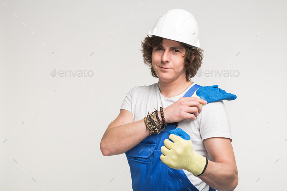 portrait of handsome curly white man in builders helmet - Stock Photo - Images