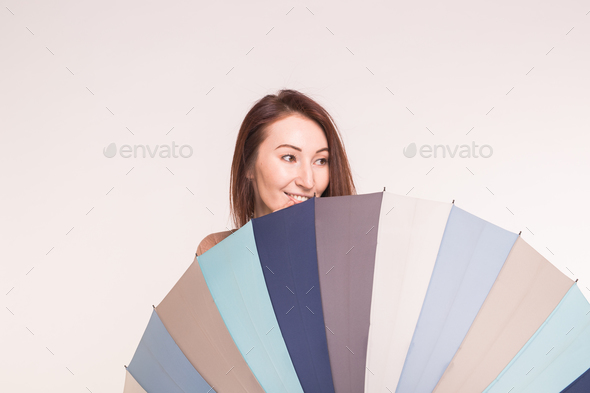 A young asian woman behind colourful umbrella on white background - Stock Photo - Images