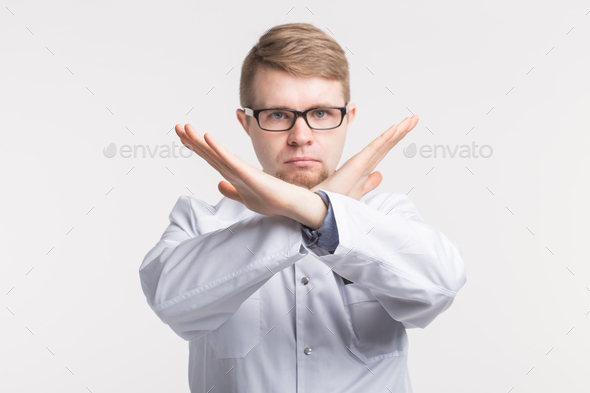 young male doctor crossing hands in forbidding gesture - Stock Photo - Images