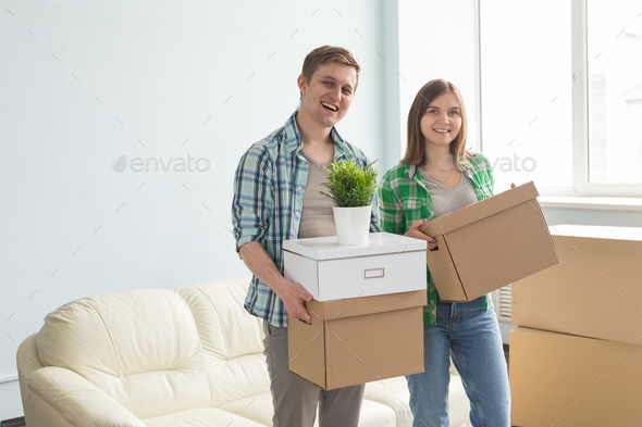Happy young couple holding moving boxes with sofa on the background. - Stock Photo - Images