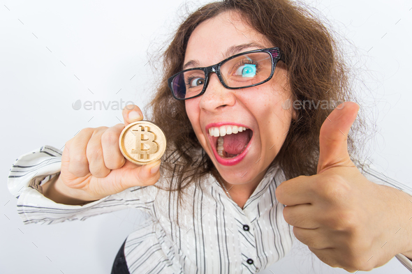 Funny woman holding golden bitcoin and showing thumbs up - successful innovative financial trend. - Stock Photo - Images