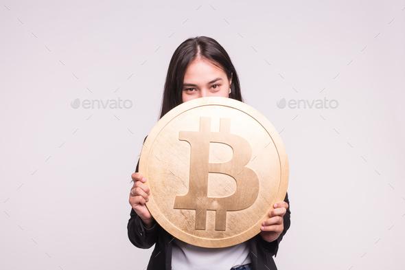 Beautiful asian girl hiding behind big bitcoin in light studio - Stock Photo - Images