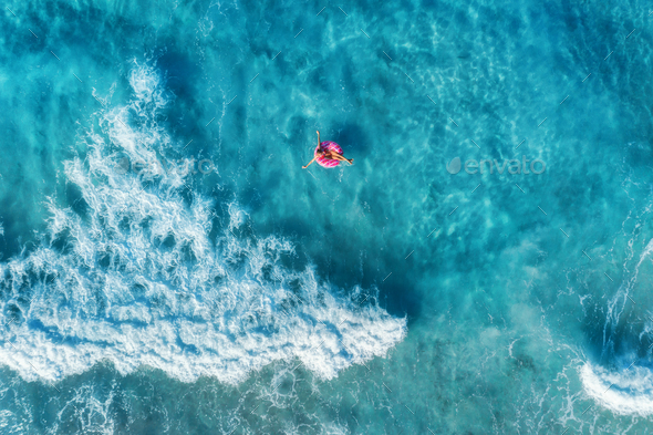 Aerial view of woman in the sea with waves - Stock Photo - Images