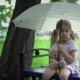 A Little Girl with a Toy Hare Sits on a Bench Under an Umbrella - VideoHive Item for Sale