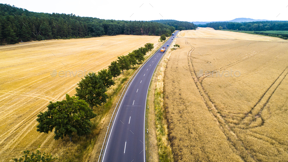 Aerial view of a country road with moving cars and trucks between agricultural fields - Stock Photo - Images