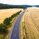 Aerial view of a country road with moving cars and trucks between agricultural fields - PhotoDune Item for Sale