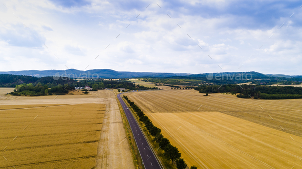 Aerial view of a country road with cars between agricultural fields in Europe - Stock Photo - Images