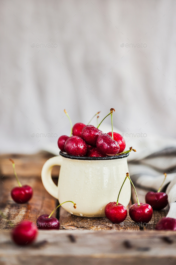 Fresh ripe cherries in a mug on rustic background - Stock Photo - Images