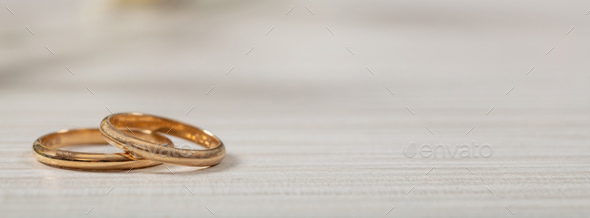 Two golden wedding rings on white wooden background, banner, copy space - Stock Photo - Images