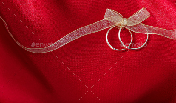 Two golden wedding rings tied with a golden ribbon on red satin background - Stock Photo - Images
