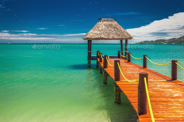 Red wooden jetty extending to tropical ocean in Fiji - Stock Photo - Images