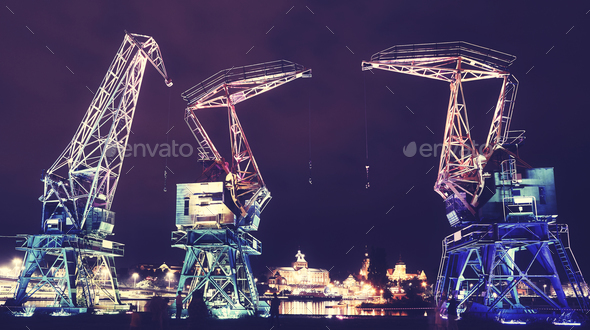 Illuminated old port cranes. - Stock Photo - Images