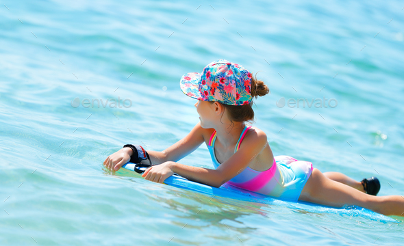 Happy little girl swimming on the bodyboard - Stock Photo - Images