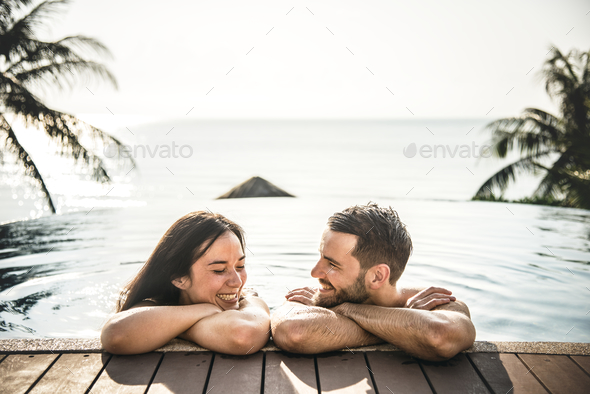 Couple relaxing in a swimming pool - Stock Photo - Images