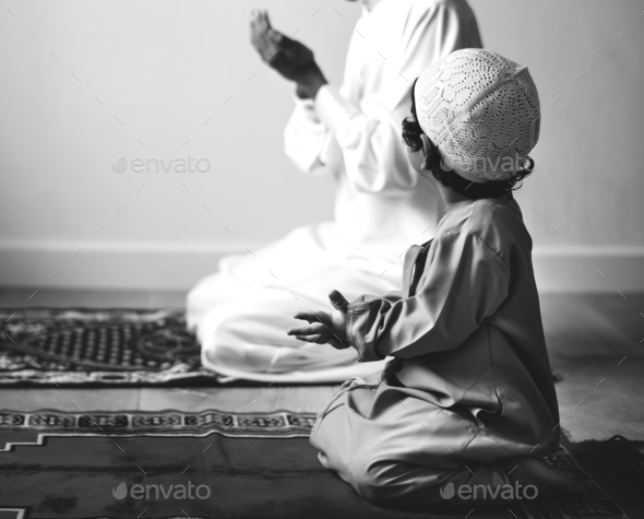 Muslim boy learning how to make Dua to Allah - Stock Photo - Images
