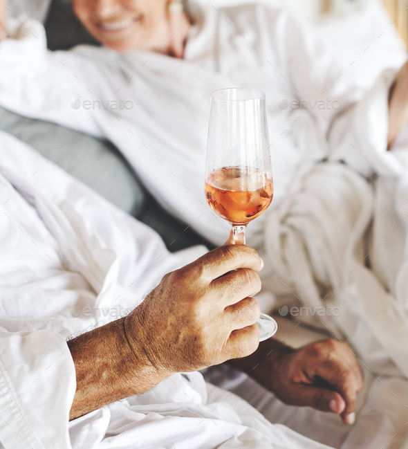 Couple having prosecco in bed - Stock Photo - Images