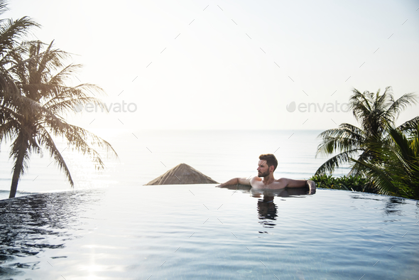 Handsome guy relaxing in swimming pool - Stock Photo - Images