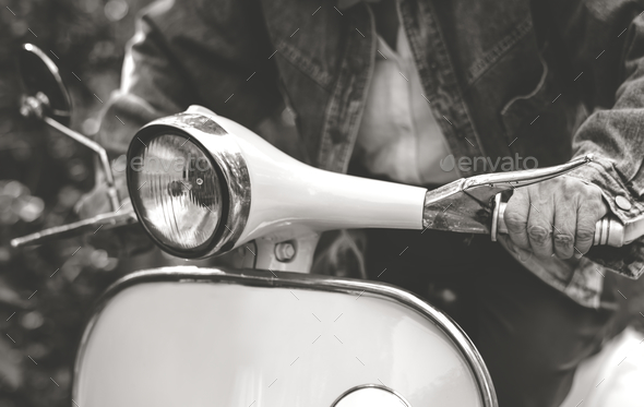 Closeup of a man riding a classic scooter - Stock Photo - Images