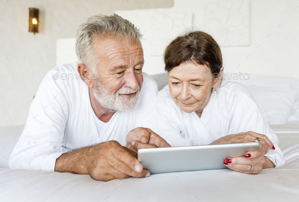 Senior couple using a tablet in bed - Stock Photo - Images