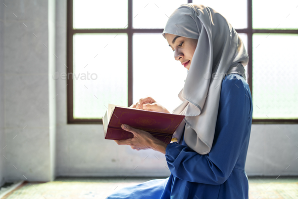 Muslim woman reading from the quran - Stock Photo - Images