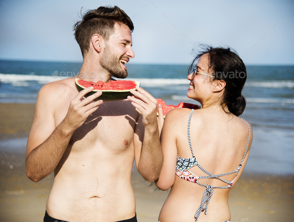 Couple eating watermelon on the beach - Stock Photo - Images