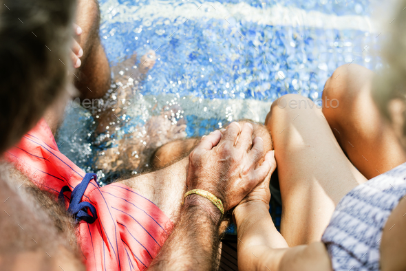 Senior couple holding hands by the swimming pool - Stock Photo - Images