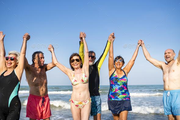 Senior friends having fun at the beach - Stock Photo - Images