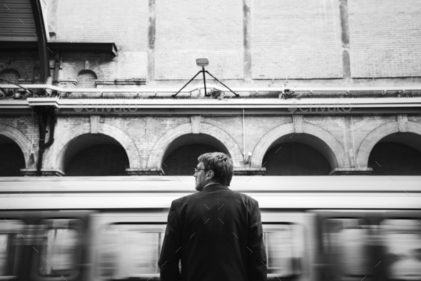 Businessman at a train station - Stock Photo - Images
