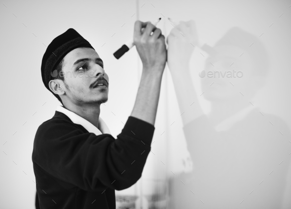 Young muslim man is writing a white board - Stock Photo - Images