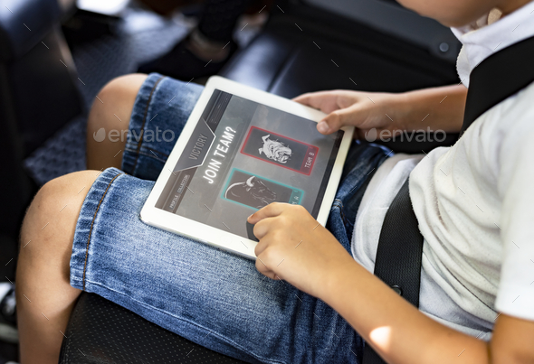 Boy playing on a digital tablet in the car - Stock Photo - Images