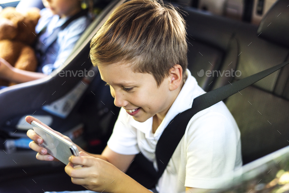 Boy playing on a smartphone in the car - Stock Photo - Images