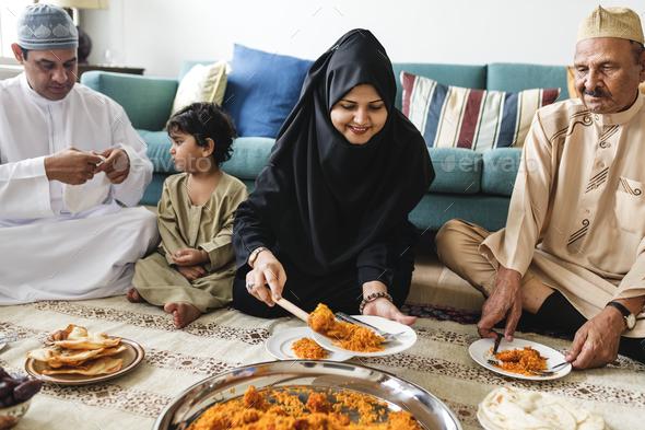 Muslim family having dinner on the floor - Stock Photo - Images
