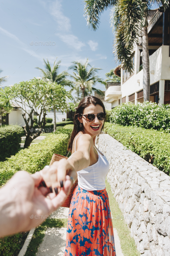 Husband following his wife on a vacation - Stock Photo - Images