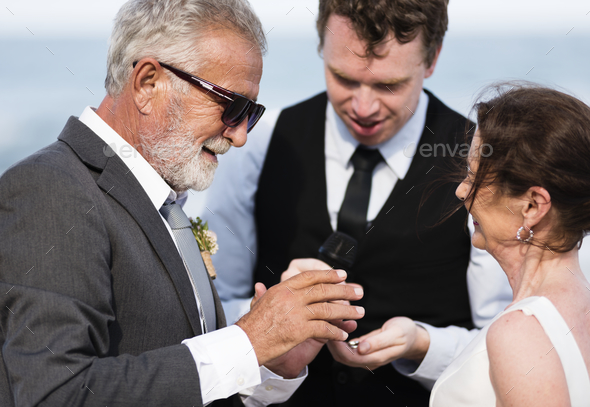 Youthful mature couple getting married at the beach - Stock Photo - Images