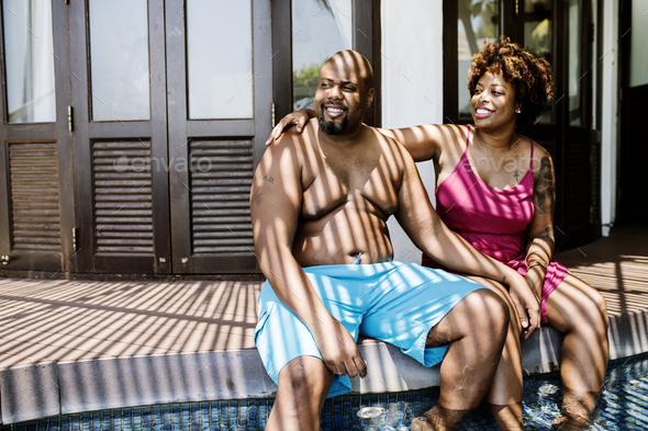 Couple sitting together at resort poolside - Stock Photo - Images