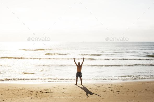 Senior caucasian man standing at the beach - Stock Photo - Images