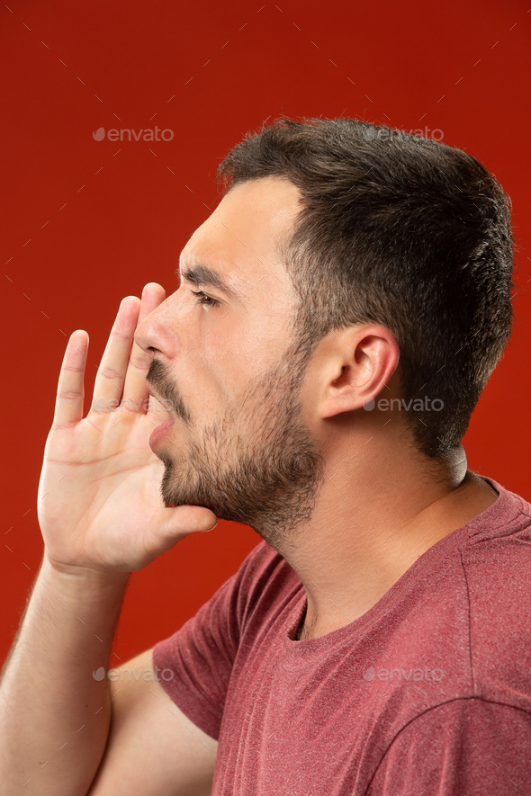 Isolated on red young casual man shouting at studio - Stock Photo - Images