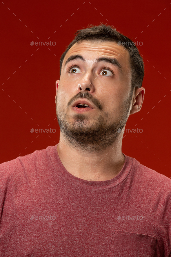 The young attractive man looking suprised isolated on red - Stock Photo - Images