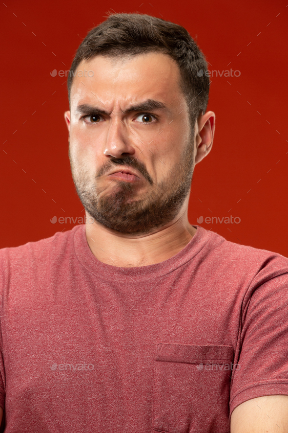 The young emotional angry man screaming on red studio background - Stock Photo - Images