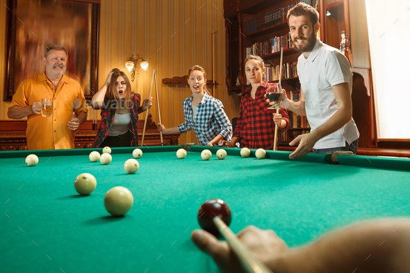 Young men and women playing billiards at office after work. - Stock Photo - Images