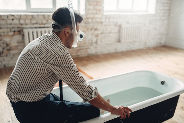 Businessman in swimming mask sitting in bathtub - Stock Photo - Images