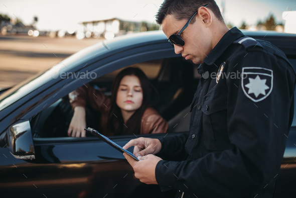 Cop in uniform checks license of female driver - Stock Photo - Images