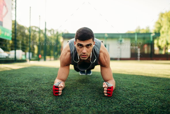 Man doing push-up exercise on a grass outdoor - Stock Photo - Images