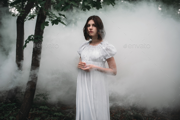 Female victim in white dress in the misty forest - Stock Photo - Images