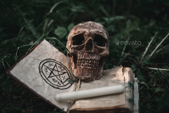 Black magic book with occult symbols and skull - Stock Photo - Images
