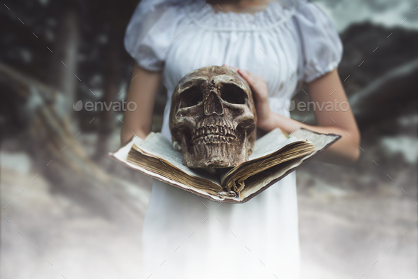 Female victim holds book and human skull in hand - Stock Photo - Images