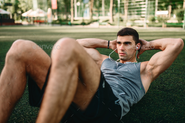 Male athlete doing exercises on the press outdoor - Stock Photo - Images